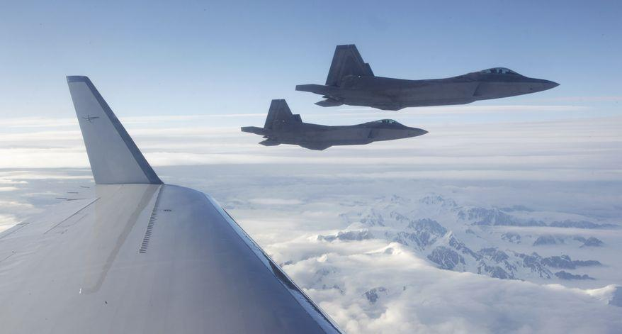 NORAD F-22s fly off a civilian airplane playing the role of a hijacked airliner over a Alaska on Aug. 10, 2010